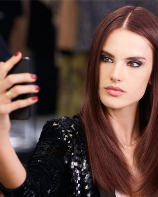Alessandra Ambrosio with long red hair taking a selfie