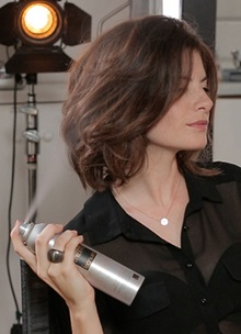 Woman spraying short brown hair with wild stylers spray